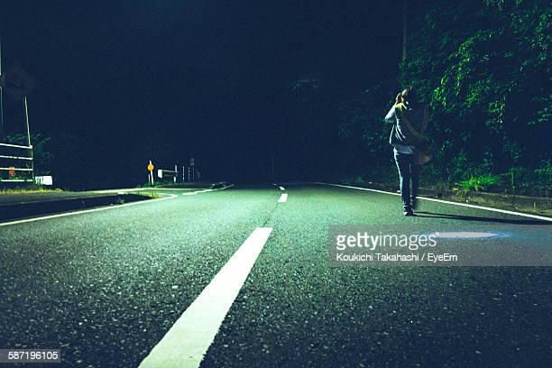Full Length Rear View Of Person Walking On Empty Road At Night