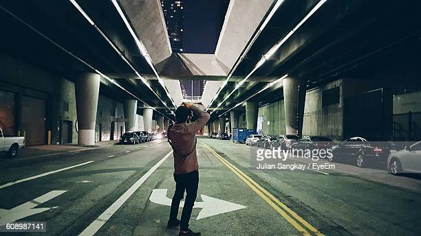 Full Length Rear View Of Photographer Photographing Bridge At Night
