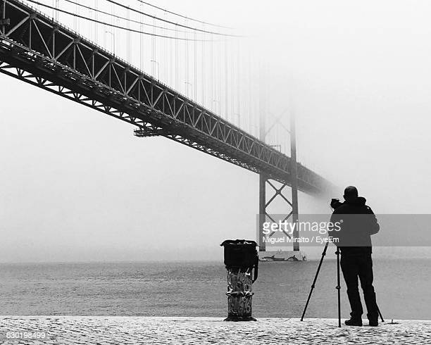 Full Length Rear View Of Photographer Standing By 25 De Abril Bridge Over Tejo River During Winter