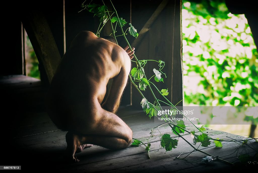 Full Length Rear View Of Sad Naked Man Crouching In Hut : Photo