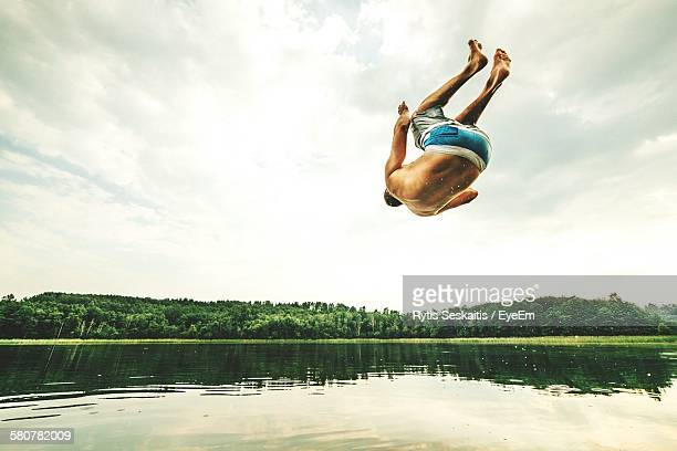 Full Length Rear View Of Shirtless Man Jumping Over River Against Sky