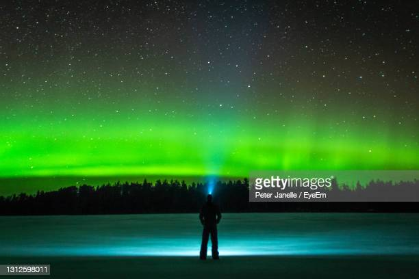 full length rear view of silhouette man standing against sky at night with northern lights - boundary waters canoe area stock pictures, royalty-free photos & images