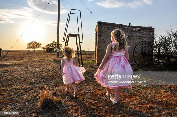 Full Length Rear View Of Sisters Walking On Field Against Sky During Sunset