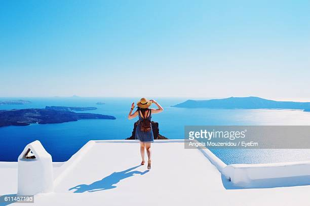 full length rear view of tourist on building terrace by sea at santorini - grécia - fotografias e filmes do acervo