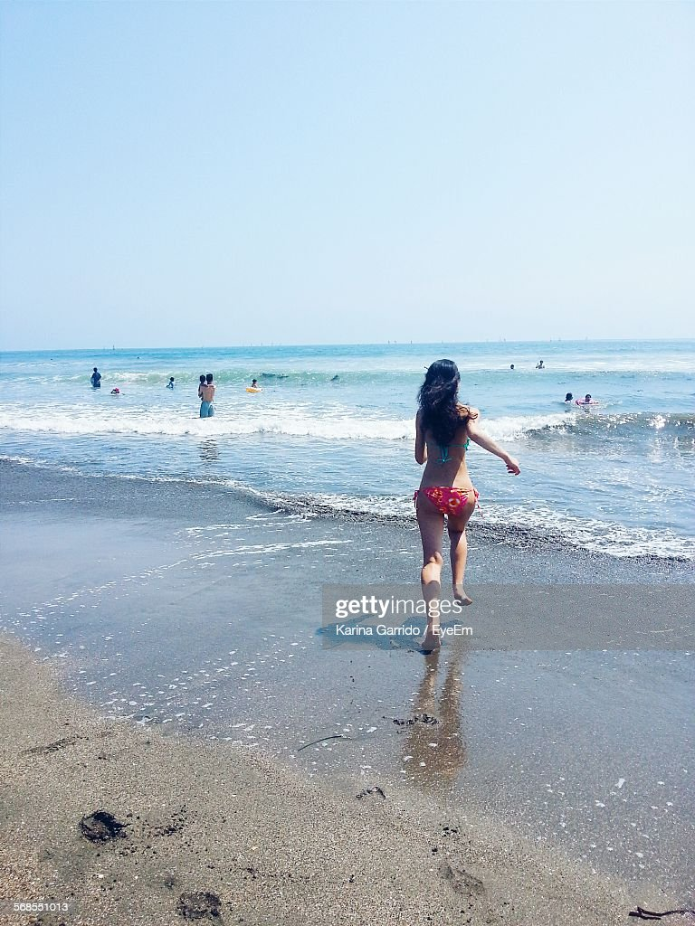 Full Length Rear View Of Woman In Bikini Running On Beach Against Clear Sky : Stock Photo