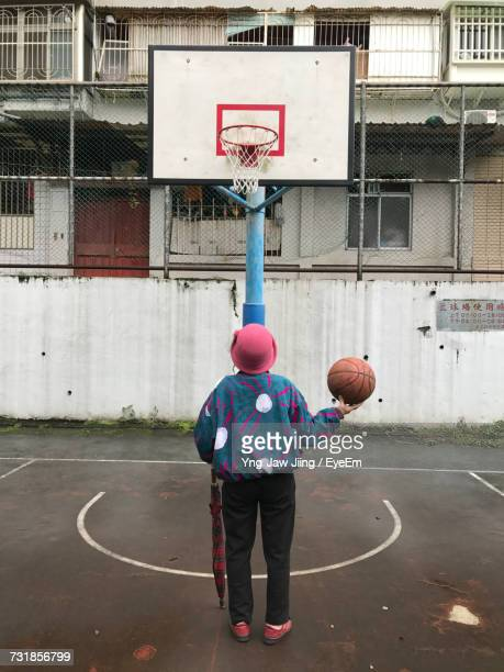 Full Length Rear View Of Woman Playing Basketball At Court