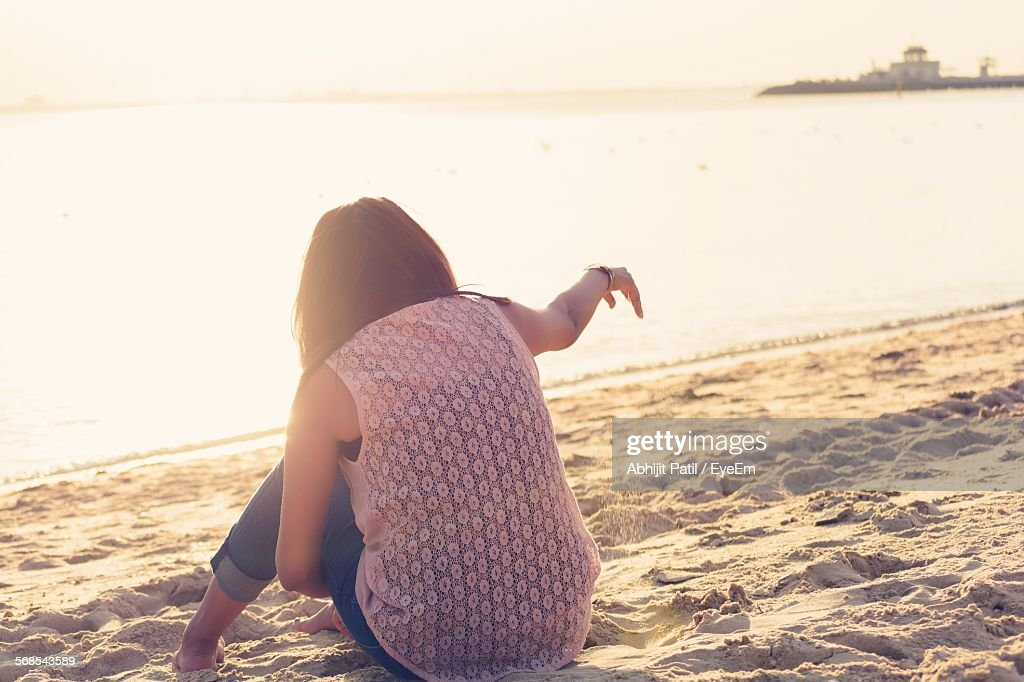 Full Length Rear View Of Woman Relaxing At Sandy Beach : Stock Photo