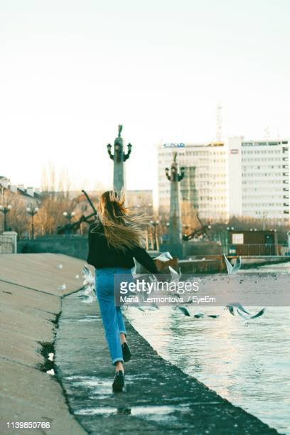 full length rear view of woman running on promenade in city against clear sky - casual clothing photos et images de collection