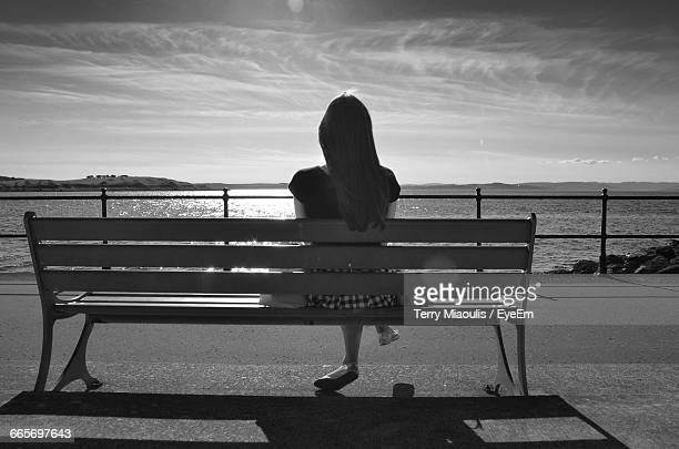 Full Length Rear View Of Woman Sitting On Bench At Sea Shore Against Sky