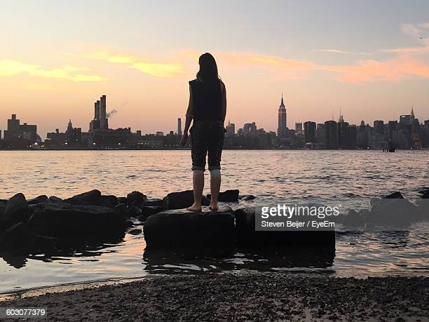 Full Length Rear View Of Woman Standing Against River In City During Sunset