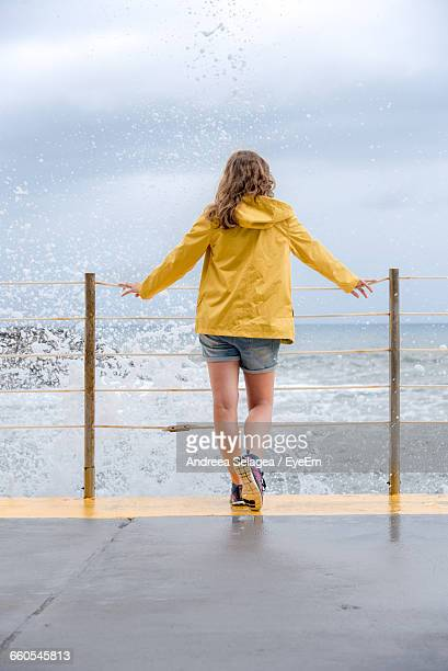 Full Length Rear View Of Woman Standing At Sea Shore Against Sky During Monsoon