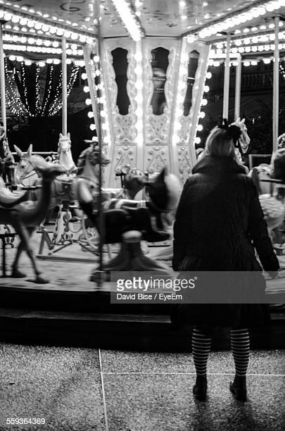 Full Length Rear View Of Woman Standing By Carousel