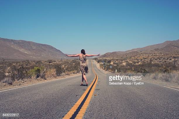 full length rear view of woman standing on country road with arms outstretched - en medio de la carretera fotografías e imágenes de stock
