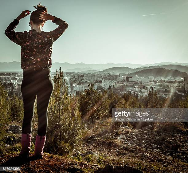 Full Length Rear View Of Woman Standing On Field By City Against Clear Sky