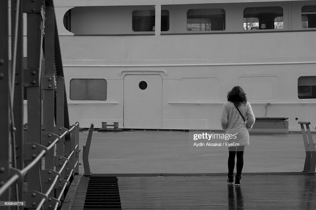 Full Length Rear View Of Woman Standing On Pier Against Ship : Stock-Foto