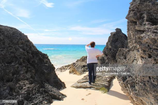 Full Length Rear View Of Woman Standing On Rock At Beach Against Sky