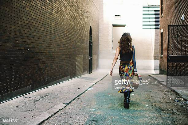 Full length rear view of woman walking down alley, Boston, Massachusetts, USA