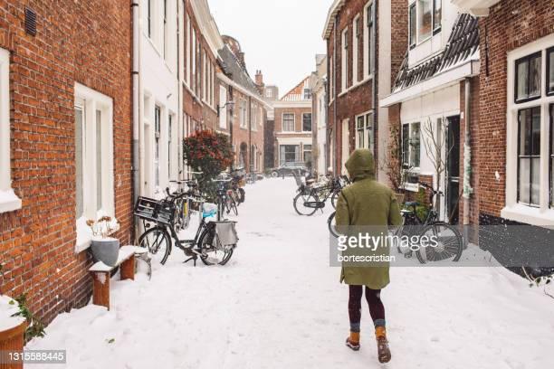 full length rear view of woman walking in city during winter - bortes imagens e fotografias de stock