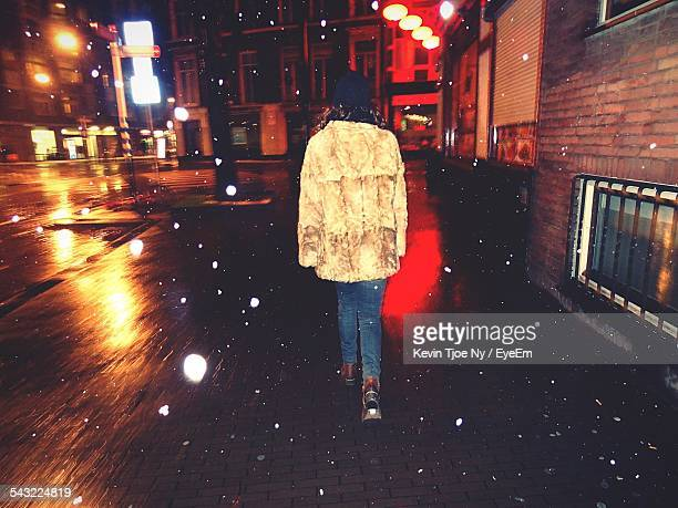 Full Length Rear View Of Woman Walking On City Street During Snow At Night