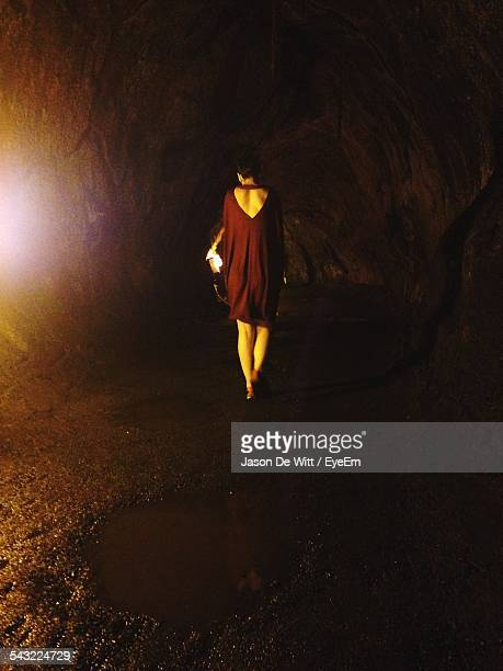 Full Length Rear View Of Woman Walking On Dirt Road At Night