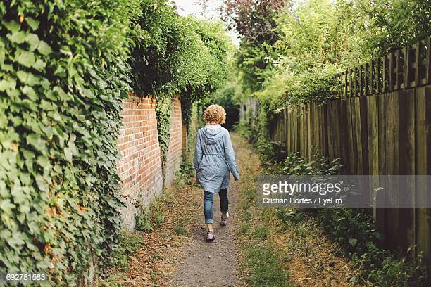 Full Length Rear View Of Woman Walking On Pathway Amidst Wall
