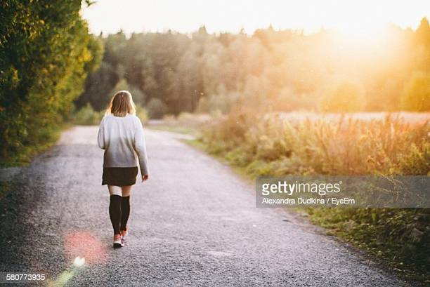 Full Length Rear View Of Woman Walking On Street By Field On Sunny Day