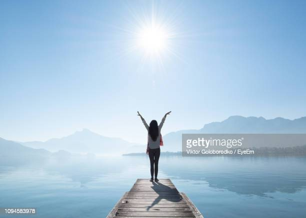 full length rear view of woman with arms raised standing on pier by lake against sky during sunny day - ruhige szene stock-fotos und bilder