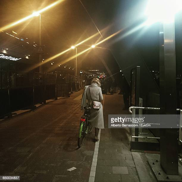 Full Length Rear View Of Woman With Bicycle On Illuminated Street At Night