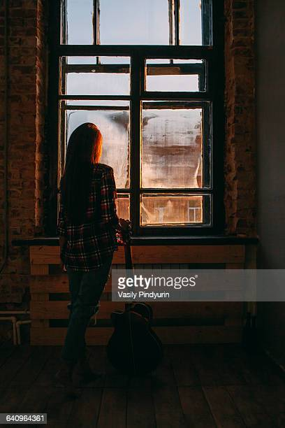 Full length rear view of woman with guitar standing by window at home
