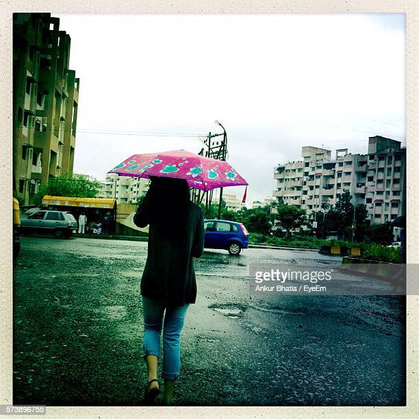 Full Length Rear View Of Woman With Umbrella Walking On Street Against Sky During Monsoon