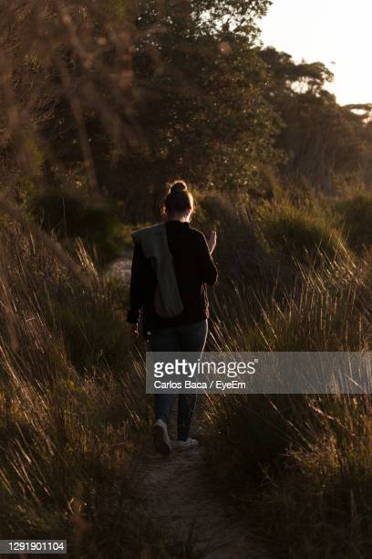 full length rear view of women walking on field - batemans bay stock pictures, royalty-free photos & images