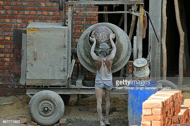 Full Length Rear View Of Worker Standing By Cement Mixer At Construction Site