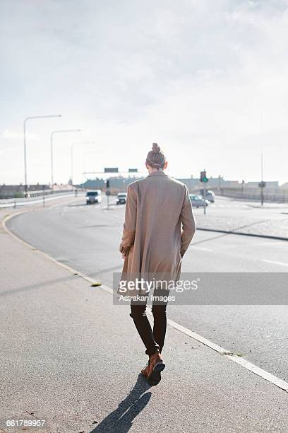 full length rear view of young businessman walking on sidewalk - coat ストックフォトと画像