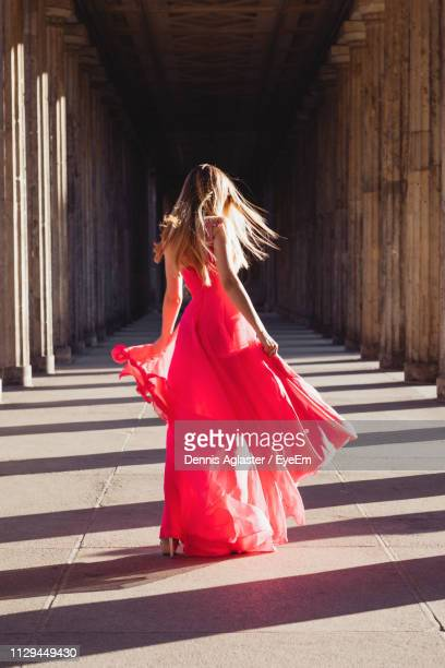 full length rear view of young woman in pink evening gown walking at colonnade - avondjurk stockfoto's en -beelden