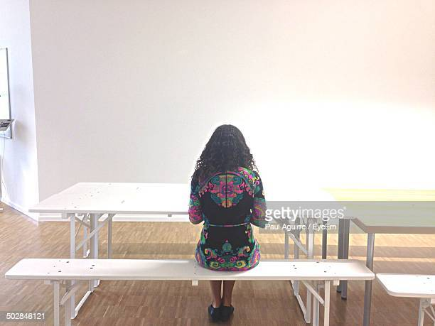 Full length rear view of young woman sitting in cafeteria