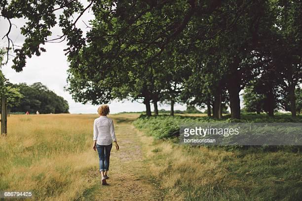 full length rear view of young woman walking on footpath - bortes imagens e fotografias de stock
