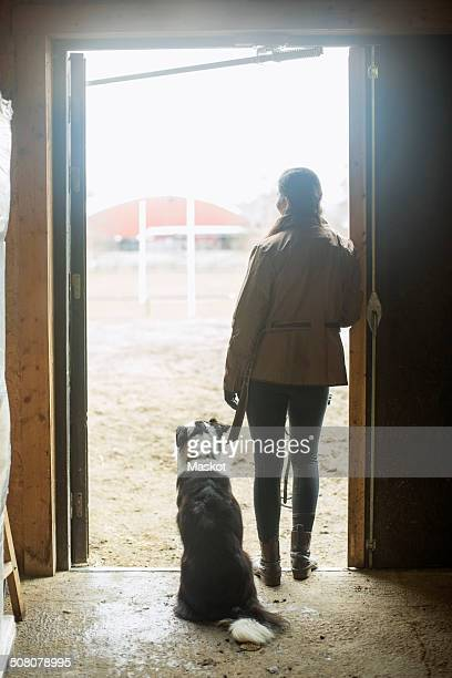 Full length rear view of young woman with dog leaning in doorway of horse stable