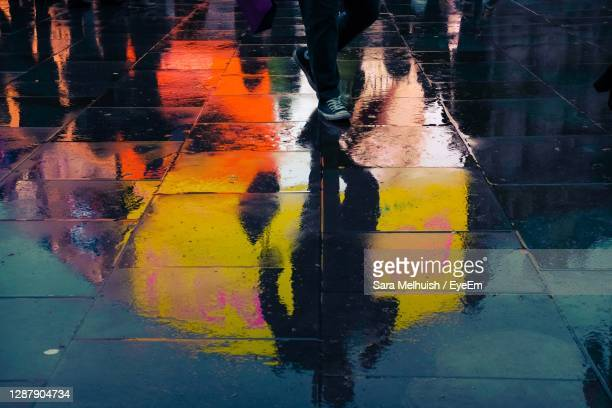 full length  reflection of person with shopping bag standing on wet pavement  in city - merchandise stock pictures, royalty-free photos & images