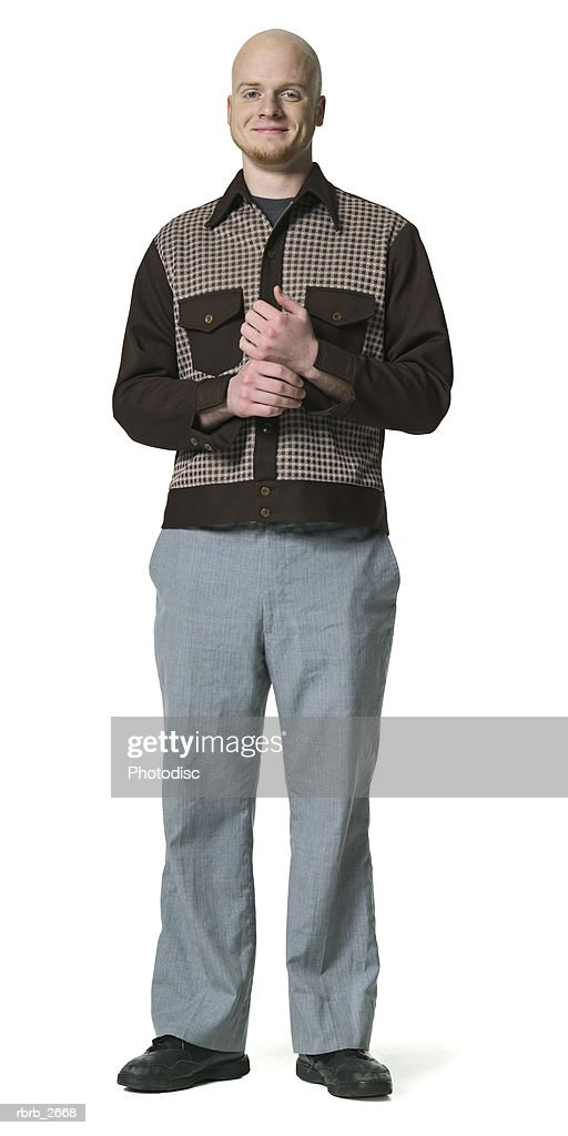full length shot of a bald young adult male in a brown shirt as he smiles at the camera : Foto de stock
