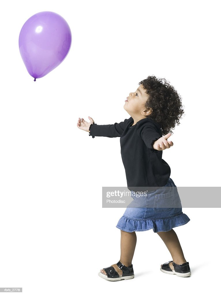 full length shot of a female child as she plays and chases a balloon : Foto de stock