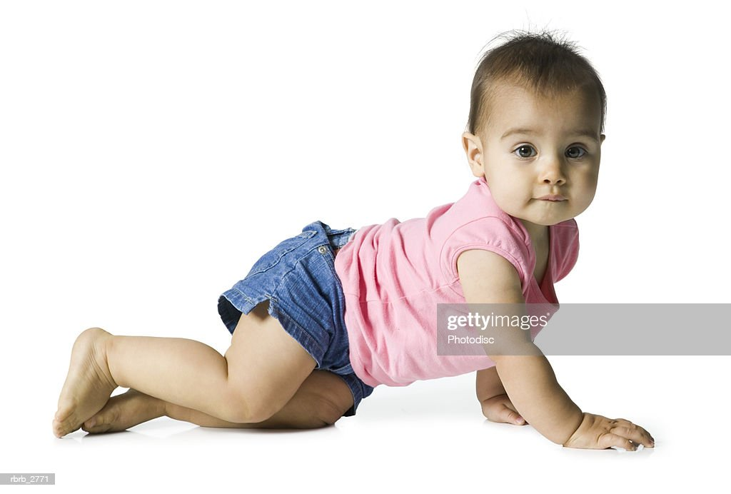 full length shot of a female infant in a pink shirt as she crawls : Foto de stock