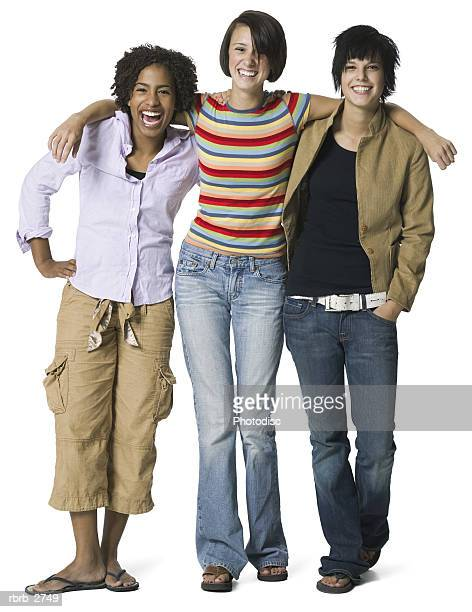 full length shot of a group of three teenage female friends as they smile at the camera