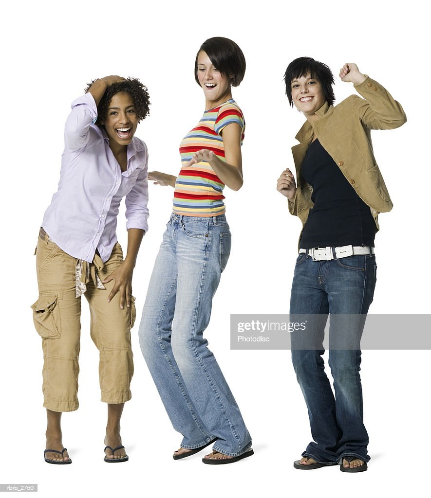 full length shot of a group of three teenage female friends as they playfully move around : Foto de stock