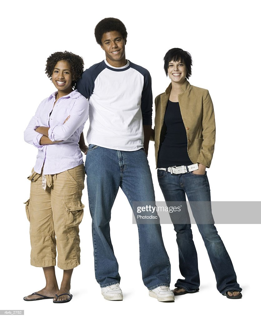 full length shot of a group of three teenage friends as they smile at the camera : Foto de stock