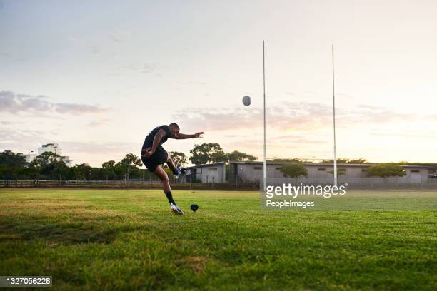 in voller länge schuss eines hübschen jungen sportlers kickt einen rugby-ball während einer frühen morgen-trainingseinheit - rugby punktversuch stock-fotos und bilder