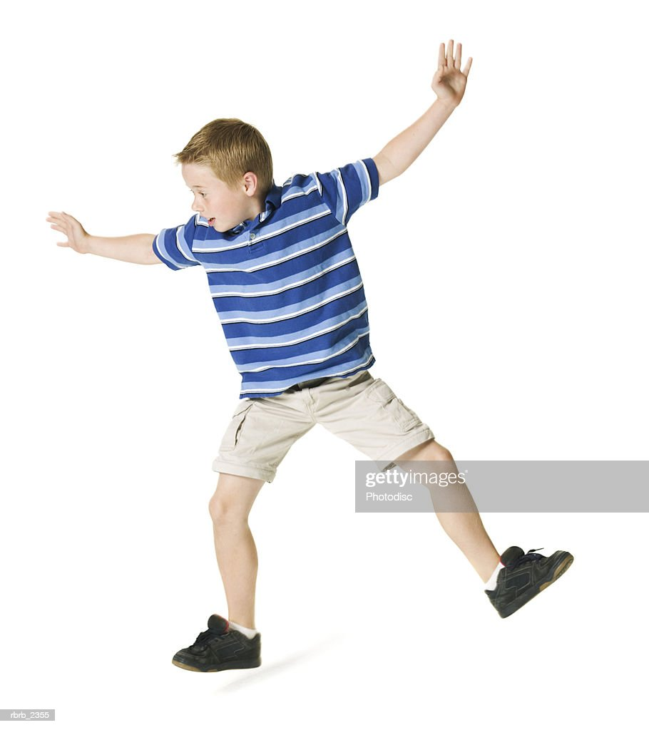 full length shot of a male child as he playfully jumps around : Foto de stock