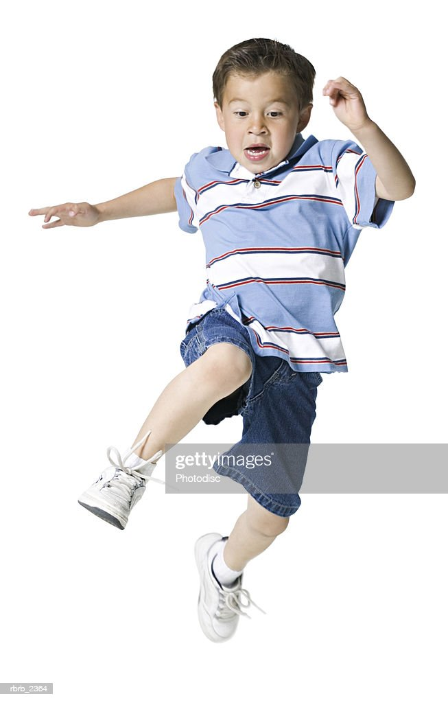 full length shot of a male child in a blue stripped shirt as he runs and jumps through the air : Foto de stock