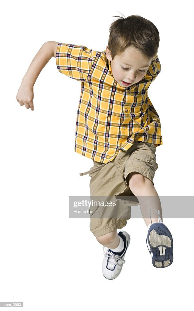 full length shot of a male child in a yellow shirt as he runs and jumps through the air : Foto de stock