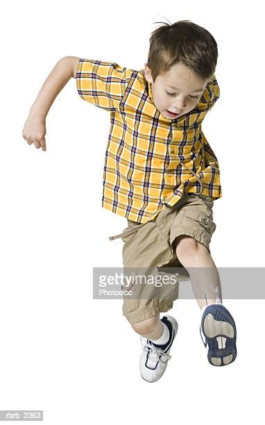 full length shot of a male child in a yellow shirt as he runs and jumps through the air