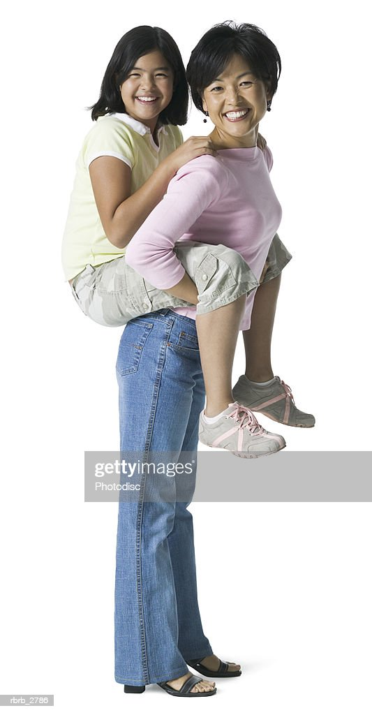full length shot of a mother as she carries her daughter on her back and smiles : Foto de stock